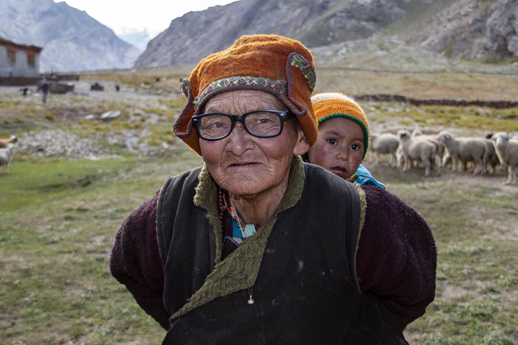 Oma hoedt schapen met kind op rug Zanskar vallei